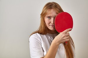 Studio indoor portrait of young girl with red hair and freckles dressed in white t-shirt holding table tennis rackets