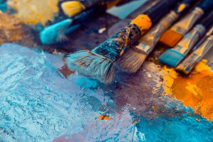 Artistic brushes on painted canvas