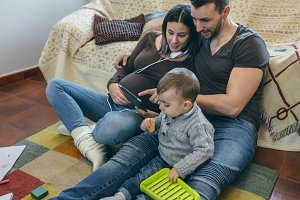 Pregnant woman and husband looking tablet while son plays