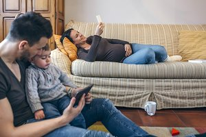 Father looking tablet with little son while the pregnant mother looks the mobile