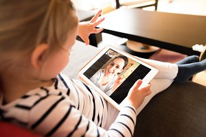 Little girl at home with tablet, video chatting with her mother.