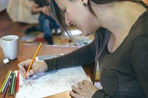 Young woman coloring mandalas