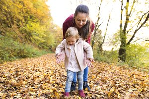 Mother and daughter on a walk in autumn forest.