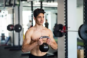 Young fit hispanic man in gym exercising with kettlebell.