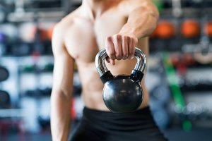 Unrecognizable young fit man in gym exercising with kettlebell.