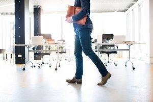 Unrecognizable businessman walking in an office.