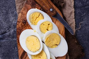 Boiled sliced chicken eggs on cutting board