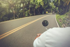 Close-up of motorcyclist riding motorbike transporting on road surrounded by summer jungle