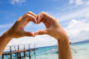 Close-up of hands putting in heart shape over beach sea scene background