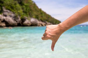 Close-up of thumbs down and dislike gesture in beach sea shore background