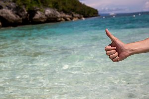 Close-up of thumbs up gesture in beach sea shore background