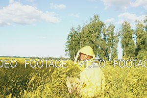 Pan shot of beekeeper man with wooden frame walking in blossom field while working in apiary