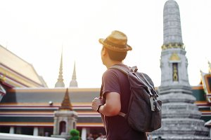 Young Asian traveling backpacker in Wat Pho in Bangkok, Thailand