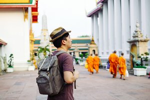 Young Asian traveling backpacker in Wat Pho with Buddhist monks walking background in Bangkok, Thailand