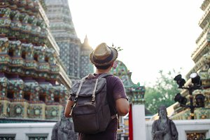 Young Asian traveling backpacker in Wat Pho with India inspired temple in Bangkok, Thailand