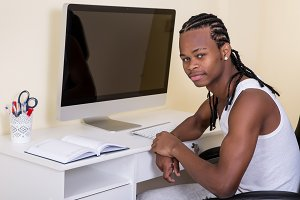 Young black man sitting at computer