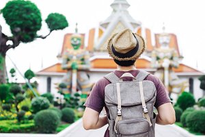 Young Asian traveling backpacker in Wat Arun with giant statues in Bangkok, Thailand