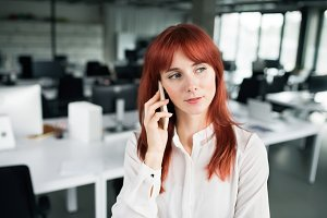 Businesswoman with smartphone in her office working.