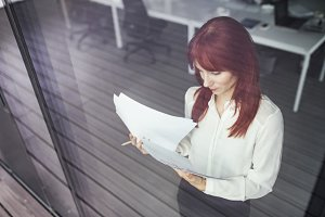 Businesswoman with documents in her office working.
