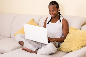 Young black man using laptop on couc