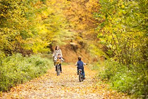 Mother with little sons cycling in autumn park.