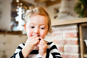 Cute little girl in striped dress eating a cookie.