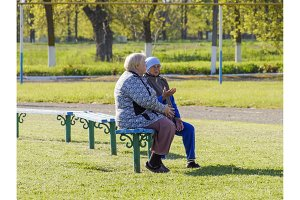 Two elderly retired women sit on a bench and discuss their lives. Life is retired. The aged people.