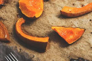 Baked slices of pumpkin on parchment