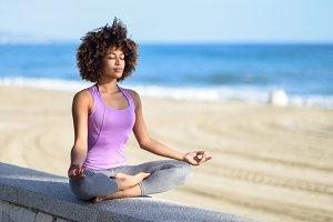 Black woman doing yoga in the beach