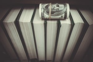 books and money in a bookcase