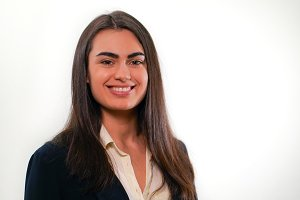 Portrait of young smiling woman in business suit on white background
