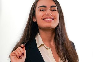 Portrait of young smiling woman touches hair in business suit on white background