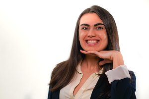 Portrait of young smiling woman putting her hand to her chin in business suit on white background