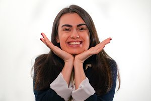 Portrait of smiling girl putting her hand to her chin in business suit on white background