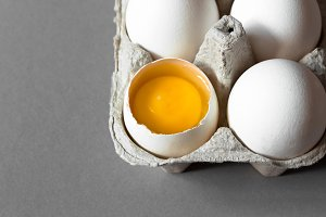 Broken egg with yolk in carton