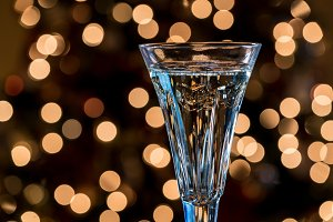 Champagne in crystal flute against christmas tree lights