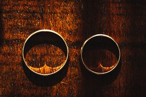 Golden wedding rings on wooden backrgound