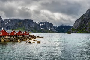 Mount Olstind above red fishing cabins in Hamnoy, Norway