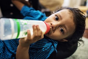 Indian boy drinking milk from bottle