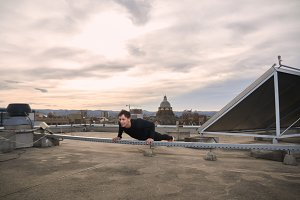 one young man, outdoors workout on rooftop, urban city roofs, rooftops behind, cityscape