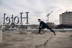 one young man workout stretching outdoors on rooftop. buildings crane behind, urban area city cityscape. Hotel sign backwards
