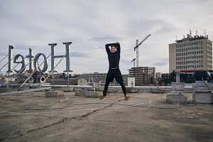 "one young man stretching outdoors on rooftop. Buildings crane behind, cityscape, urban area. ""Hotel"" sign spelled backwards."