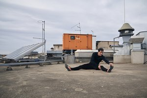one young man stretching outdoors on rooftop of building. Heating, ventilation, and air conditioning systems.