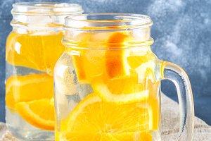 Orange detox water in mason jars on a gray concrete background. Healthy food, drinks.