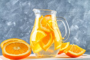 Orange detox water in a pitcher on a gray concrete background. Healthy food, drinks.