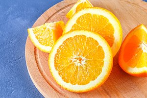Orange slices on a wooden board on a concrete gray background. Healthy food.