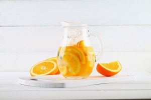 Orange detox water in a jug on a white wooden table. Healthy food, drinks.
