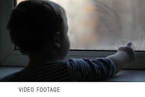 Little boy watching window