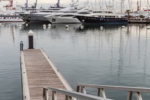 White yachts in  harbor. Wooden pier