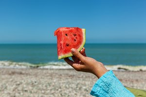 Watermelon in hand against the sea.